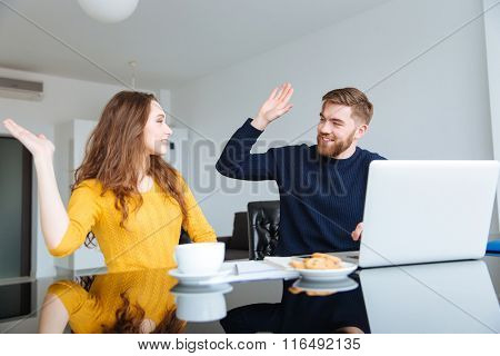 Portrait of a happy couple giving five sign with palms at home