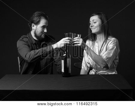 Man And Woman Are Boozing, Bottle On The Table, Keeping Glasses, Smiling.