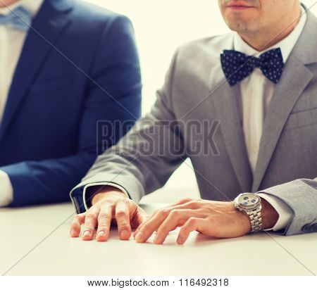 close up of happy male gay couple hands on wedding