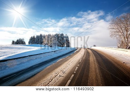 Asphalt road in snowy winter on beautiful sunny day