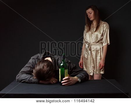 Drunk Man Is Sleeping On The Table With The Bottle In The Hand, His Wife Standing Behind