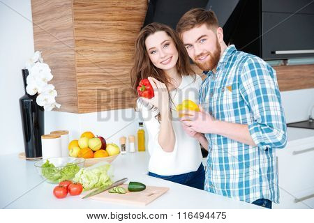 Beautiful cheerful young couple cooking healthy food on the kitchen together