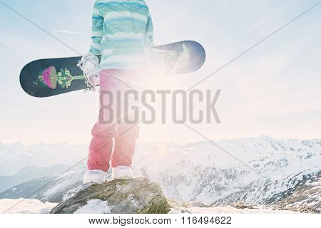 Close up of female snowboarder wearing blue jacket and pink pants standing with snowboard in her hands and enjoying sunny alpine mountain landscape - snowboarding concept