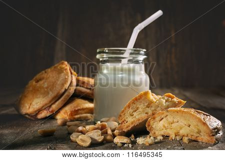 Cookies with nuts and a bottle of milk on wooden table