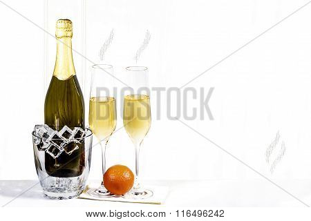 Bottle Of Champagne In Ice Bucket And Two Glasses With Mandarin Are Standing On A White Napkin