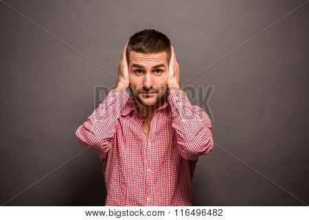 Man covering his ears