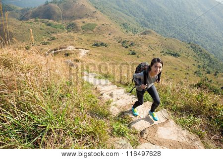 Happy smiling woman hiking in mountains