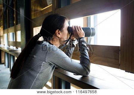 Woman watching bird though binocular