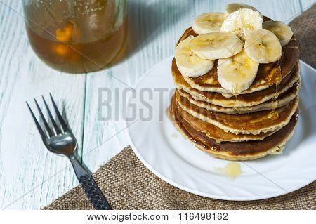 Stack of homemade pancakes with banana slices and honey on white plate with fork and linen napkin on