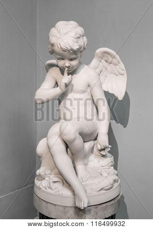 young and sad Angel sitting on a pillar