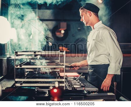 Young male cook preparing meal on the grill in kitchen