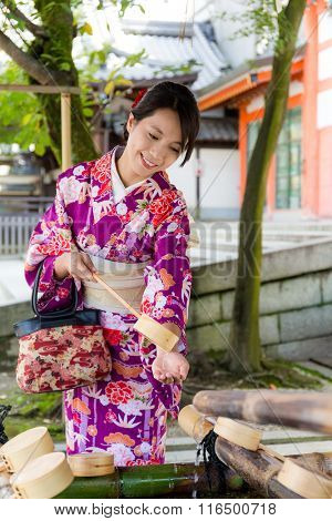Japanese woman washing hand before go inside the temple