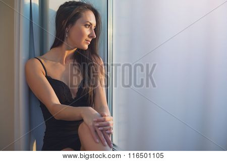 Lovely woman sitting and looking through a window admiring sunrise or sunset.