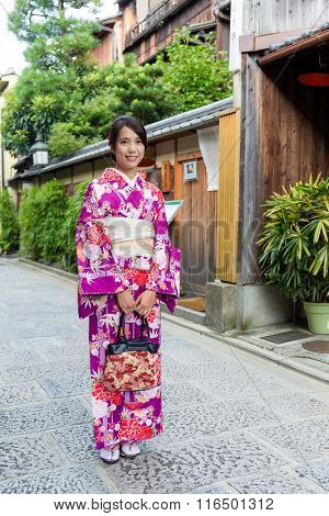 Young woman wearing kimono and standing at street