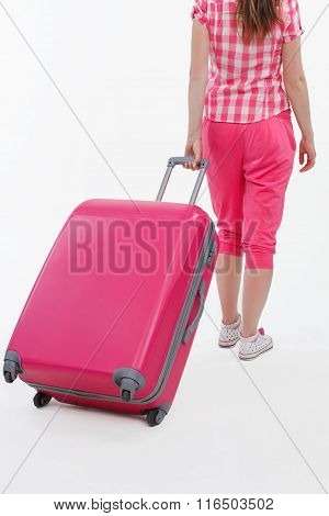 Pink travel bag and traveller girl holding it.
