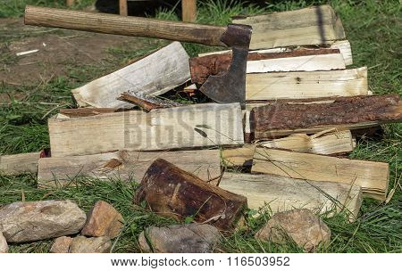 Cut Firewood And Old Axe On Green Grass. Environmental Concept