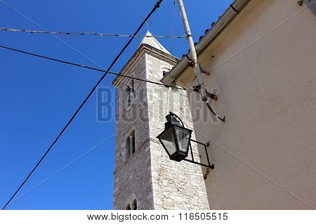 Renaissance belfry against blue sky with lantern on the wall