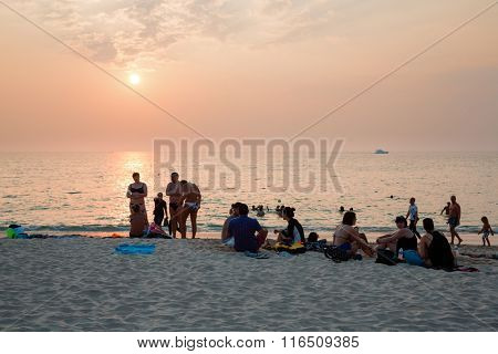KATA BEACH, THAILAND - CIRCA FEBRUARY, 2015: People relax on the beach at sunset. This is one of the most popular beaches among tourists in Phuket.