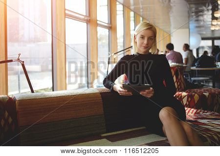 Female owner of coffee shop with digital tablet while waiting waiters for conducting interview