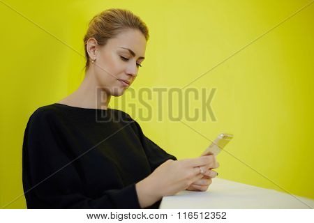Confident female entrepreneur checking email via cell telephone while standing in office interior