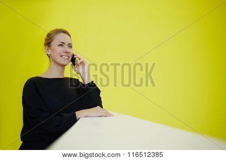 Happy female director talking on mobile phone during break