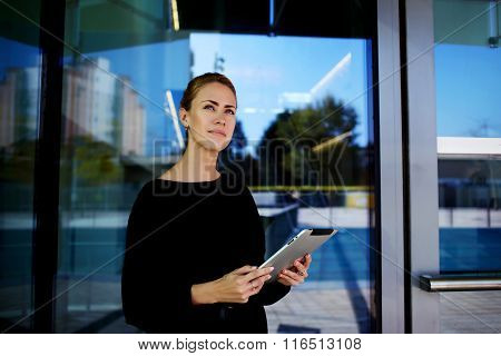Young businesswoman holding touch pad in hands and looking away during break outdoors
