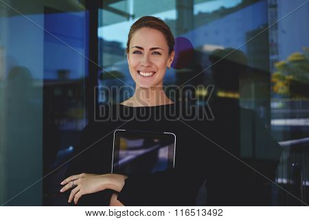 Smiling female assistant standing outdoors with touch pad during work break