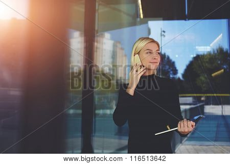 Businesswoman hold touch pad while calling with cell telephone to her partner