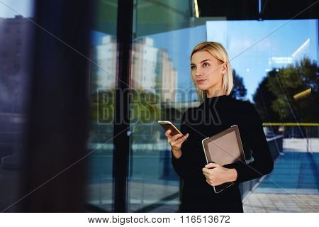 Female lawyer waiting for mobile phone call after use touch pad while standing outside company