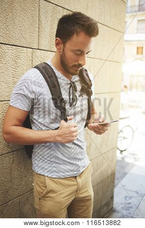 Hipster guy with a backpack on his shoulders reading text message on cell telephone