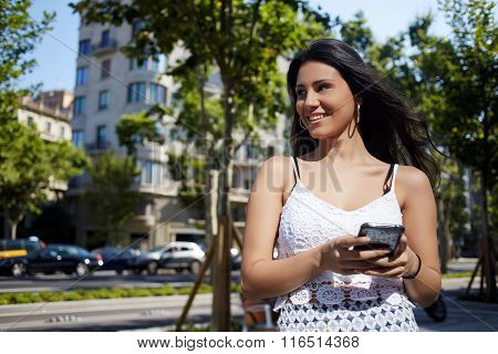 Young happy female waiting for a call on cell telephone during strolling in unfamiliar city
