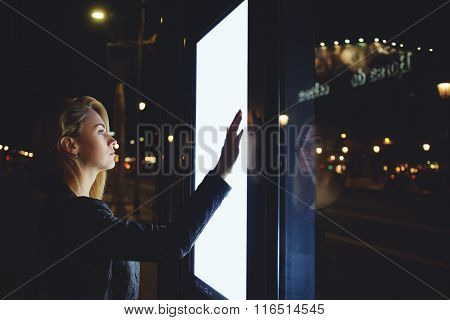 Pretty female watching movement of buses on electronic bulletin board in unfamiliar city
