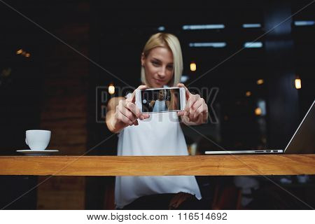 Attractive hipster girl making self portrait with mobile phone camera during rest in cafe