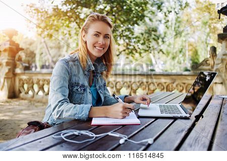 Young woman smiling to the camera while sitting with notepad and laptop computer in city park