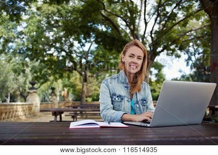 Young woman with beautiful smile posing during work on portable net-book on a campus