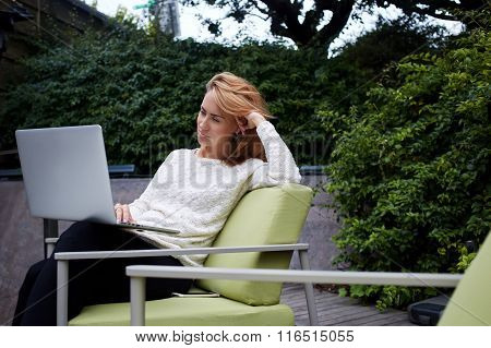 Young cute woman watching movie on laptop computer while waiting her friends in coffee shop outdoors