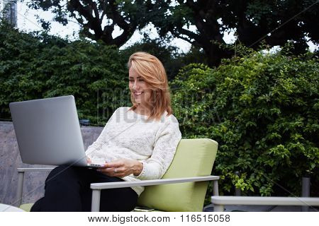 Cheerful woman watching funny video on laptop computer while waiting for her order in sidewalk cafe