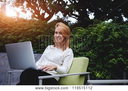 Attractive woman with cute smile sitting with open net-book at modern coffee shop in warm spring day