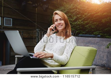 Cheerful female having pleasant conversation via cell telephone after work on net-book