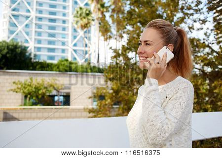 Happy Caucasian female talking via cell telephone about something funny while relaxing outdoors