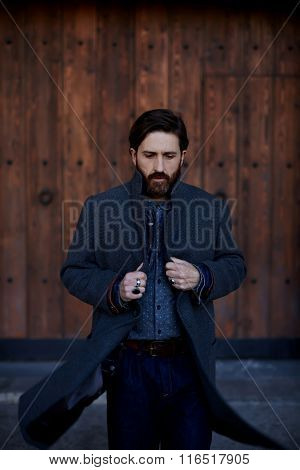 Adult successful businessman with beard dressed in stylish clothes walking outdoors