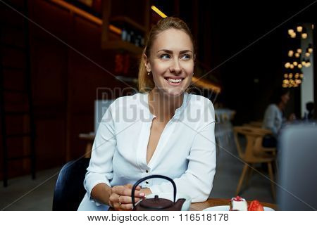 Cheerful woman looking away while relaxing in cozy coffee shop after walking