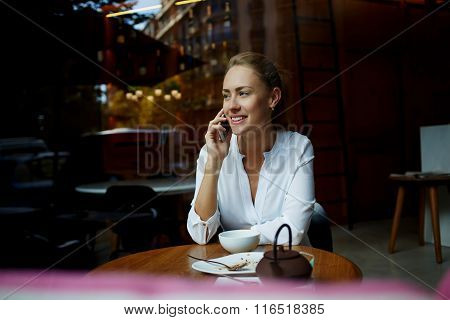 Young happy female calling with cell telephone while relaxing in modern restaurant after hard work