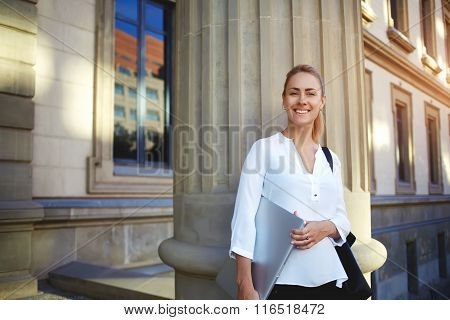 Cheerful female student with portable net-book in hands posing after lectures near University