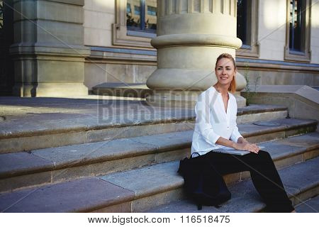 Thoughtful female traveler relaxing outdoors after watching film on portable laptop computer
