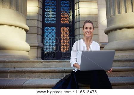Cheerful female student learning via laptop computer before lectures in University
