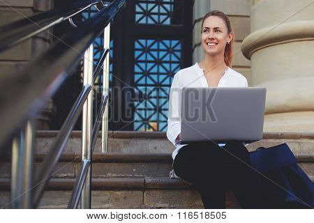 Smiling young woman enjoying good day while sitting with open net-book on stairs outdoors