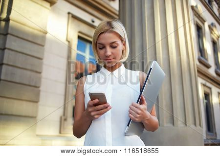 Young female holding laptop computer in hand and writing text message on mobile phone