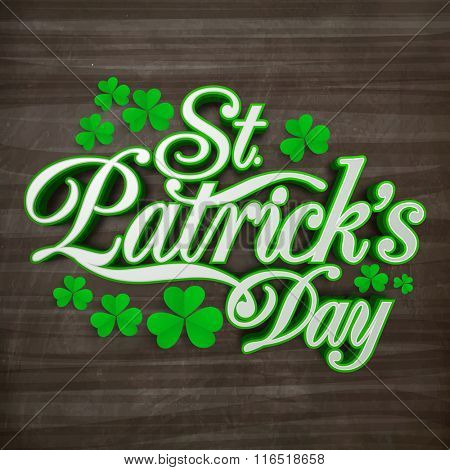 Stylish text St. Patrick's Day with beautiful shamrock leaves on wooden background.