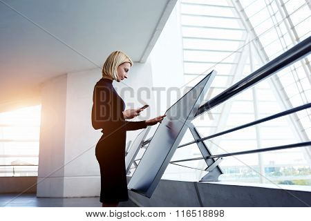 Female holding cell telephone while viewing 3d-visualization of project on digital touch screen